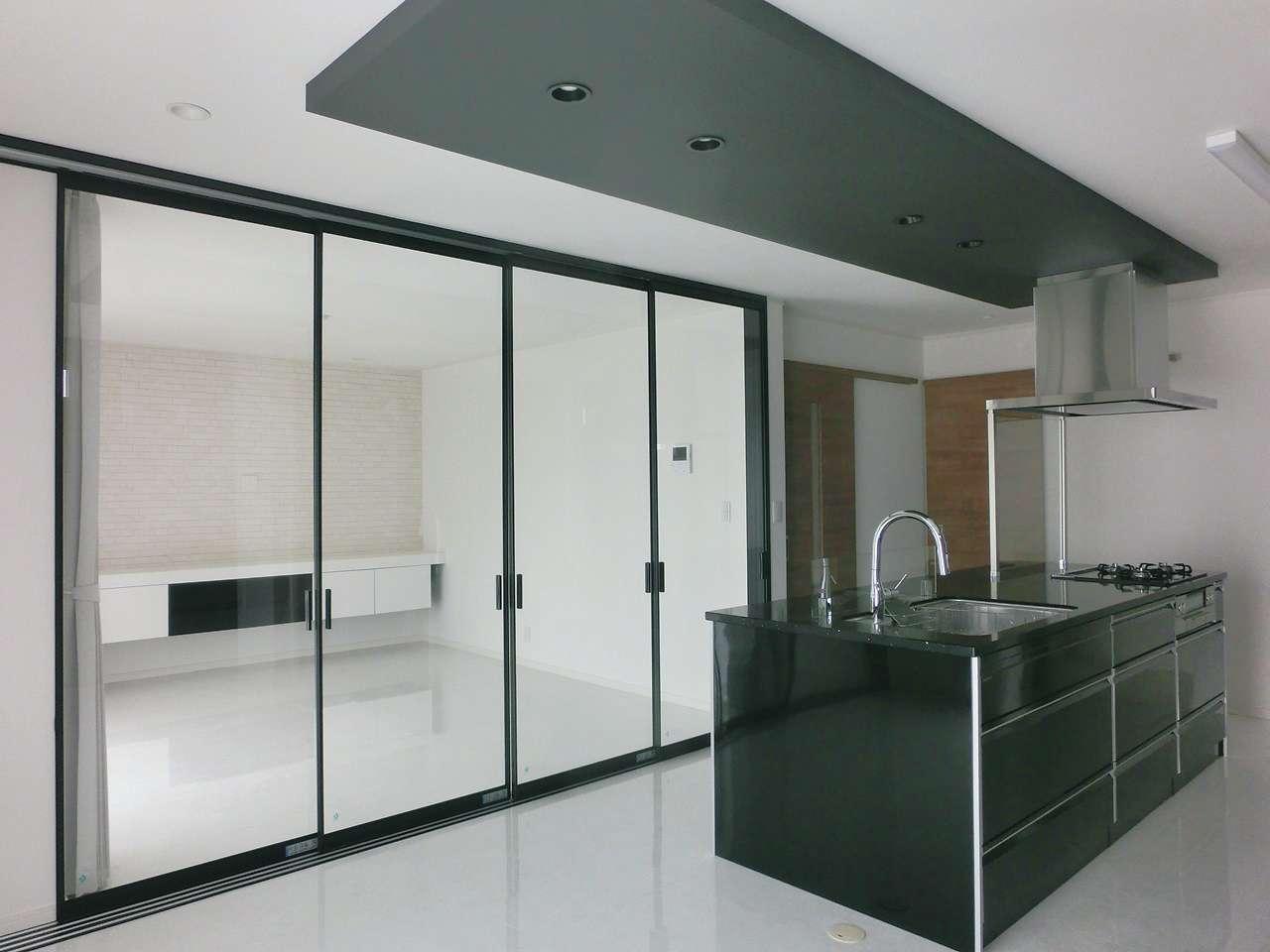朝日住宅【デザイン住宅、高級住宅、インテリア】リビングとの境目には、こだわり抜いたガラス戸が存在感を放つ。光が通り抜ける開放感と、ドアを閉めて空間を仕切れる利便性が共存