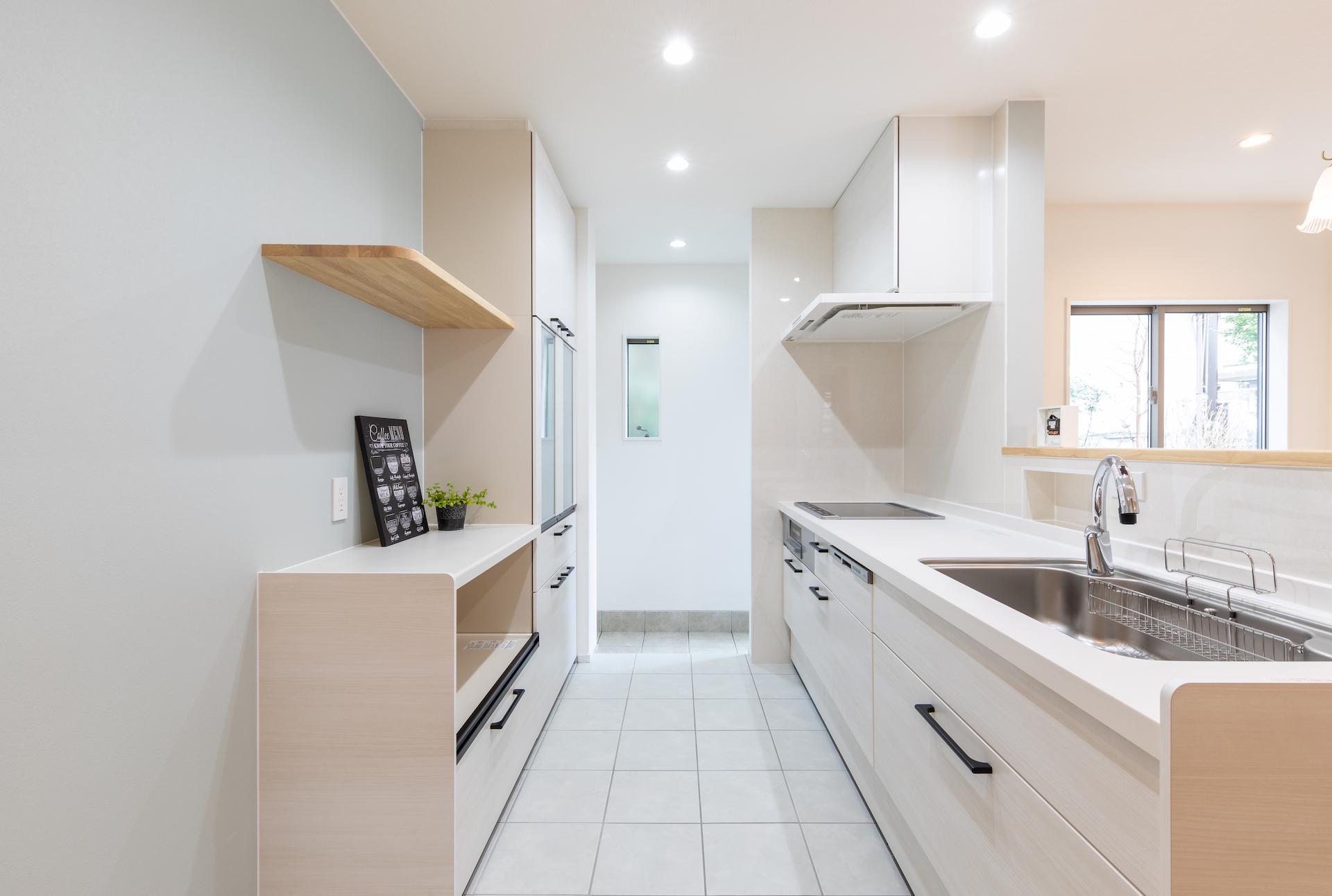 キッチンの作業台にはスパイスニッチを設けた。床は掃除のしやすさを考慮しタイルを敷きつめている。奥の一段下がった土間部分にはあえて床暖房を入れず、実家から届く野菜の保管スペースとしても活用。勝手口とつながっており、毎日のゴミ捨てもラクラクだ