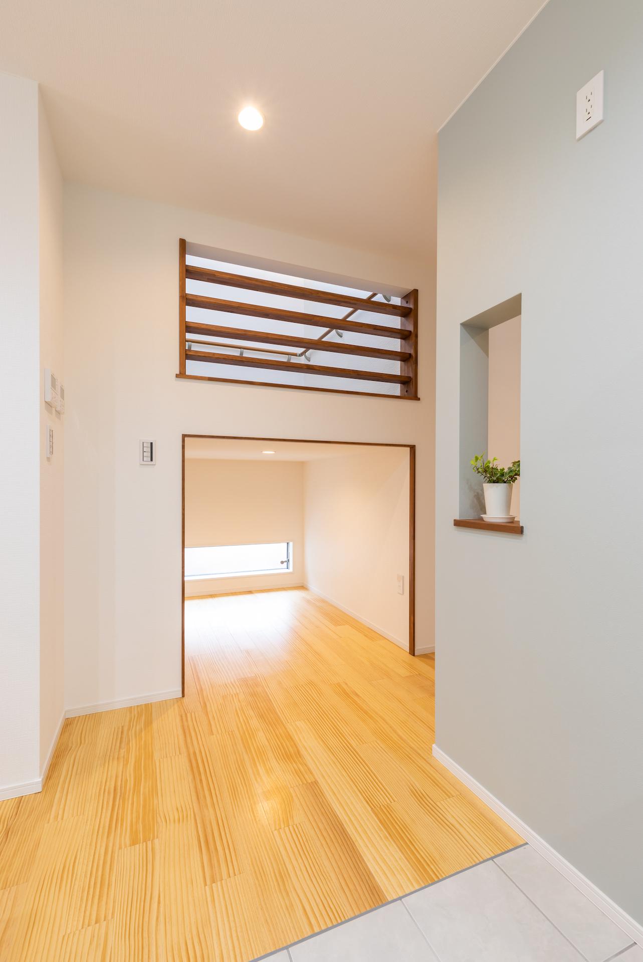 キッチン裏にある廊下に光が通るよう、壁の一部をくりぬいている。階段下には収納スペースを確保。季節ものなど、多くを収納可能だ。階段部分にはスリットを設け、家族の気配と光を伝える