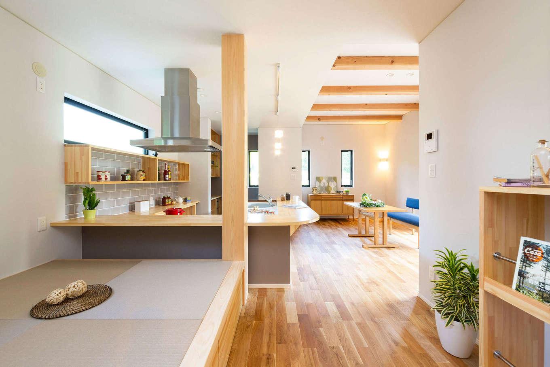 みずしまの家/水嶋建設【収納力、自然素材、間取り】カフェスタイルのオープンキッチンを中心としたモダンなLDK。柔らかな曲線を描くカウンターは造作で、キッチンに立つ奥さまと畳コーナーに座る子どもの目線が合うように工夫した。リビングは天井を上げ、意匠的に梁を見せることで心が癒される