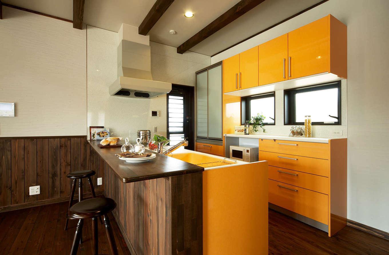 みずしまの家/水嶋建設【子育て、自然素材、インテリア】奥さまの好きなオレンジが空間の差し色になったキッチン。忙しい朝はカウンターで食事したり、夜はバーカウンターにもなる