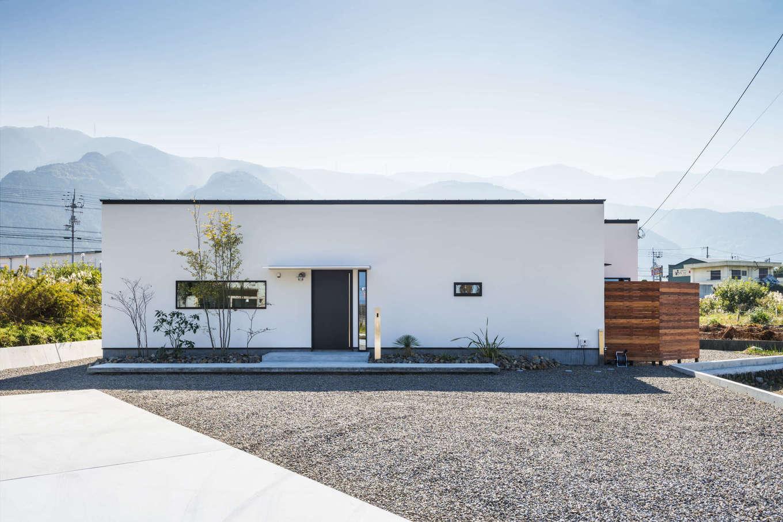 シンプルモダンな箱型の外観に、黒縁の窓枠が映える。ウッドフェンスの中には坪庭がある