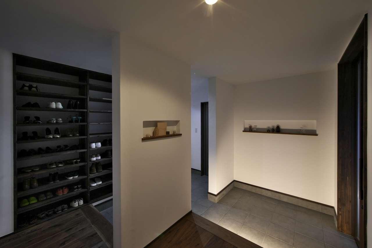KANAZAWA STYLE/金澤建築【デザイン住宅、自然素材、間取り】ゆったり広々とした玄関ホール。大容量のシューズクロークを造作し、靴脱ぎ場をゲスト用と家族用に分けたことで、空間は常にすっきり。ニッチに小物や写真を飾り、季節感を暮らしに取り入れている
