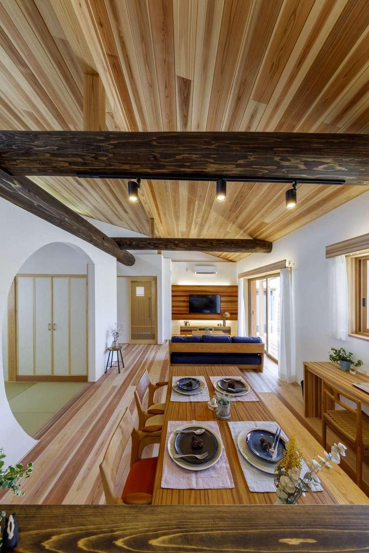 KANAZAWA STYLE/金澤建築【自然素材、平屋、ガレージ】20畳のLDKは勾配天井を採用したことで、より広く感じられる。同社の特徴である丸太梁が空間のアクセントに。R型にくり抜いた遊び心豊かな和室に心が癒される。PCカウンターも造作