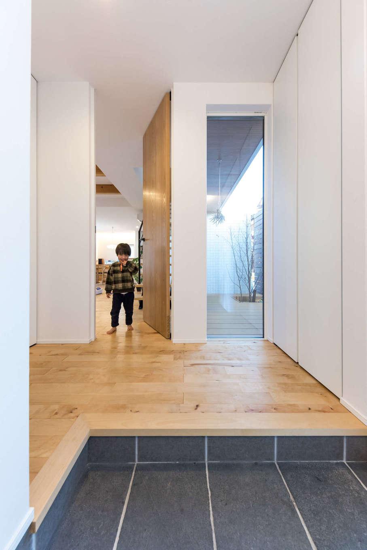 収納もドアも天井の高さに揃った玄関はスッキリとした空間。帰宅時は窓に映るインナーコートが気分をやわらげてくれる