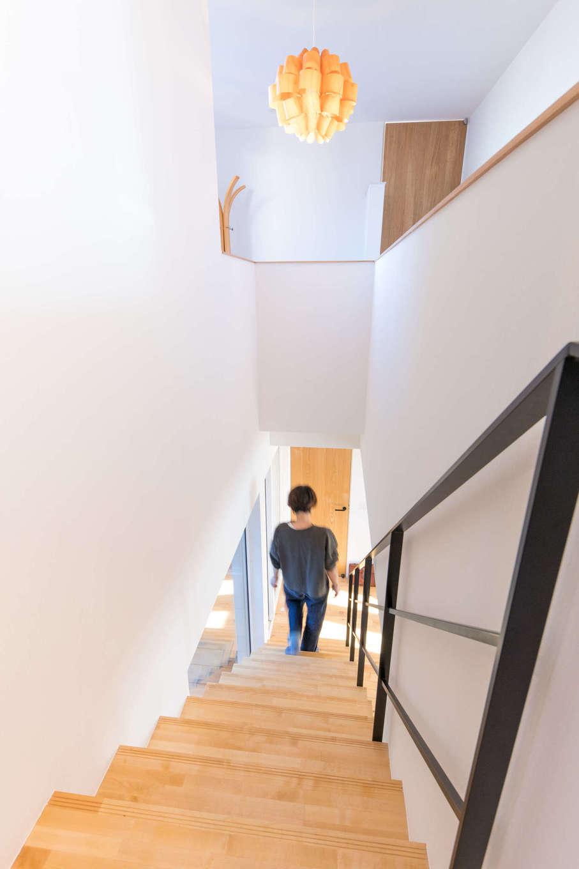 以前の住まいから使っていたという照明がアイアンのスケルトン階段によく似合う。階段上のホールには、奥さまと娘さんが使うピアノを置く予定