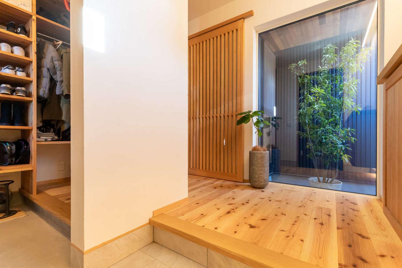 ツリーズ【デザイン住宅、自然素材、間取り】玄関を入って正面にFIX窓を設け、坪庭へと視線が抜ける。靴脱ぎ場を家族用とゲスト用に分けたことで、散らかりがちな玄関ホールがいつもすっきり。玄関クローゼットには外着用のハンガーパイプも設置