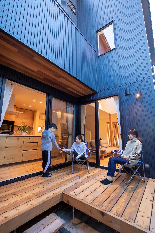 ツリーズ【デザイン住宅、自然素材、間取り】外からの視線を遮りながらBBQや水遊びなど、多用途に楽しめる中庭。L字形のウッドデッキは、外と中をつなぐアウトドアリビングとして大活躍。ガルバリウム鋼板と無垢板のコントラストもすてき