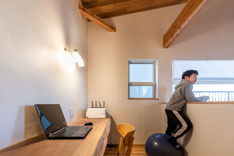 ツリーズ【デザイン住宅、自然素材、間取り】2階のデッドスペースを活かして造った一枚板のカウンター。夫婦がPCをしたり、子どもたちが勉強したり、家族共有の多目的スペースになった。吹抜けを通して、1階とのコミュニケーションもスムーズ