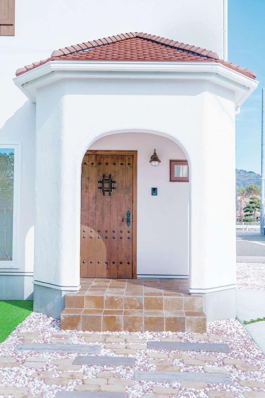 フェアリーホーム【焼津市八楠2-26-4・モデルハウス】アーチ壁に輸入ドアが映える玄関ポーチ。塗り壁と木の素材感が落ち着きを感じさせる