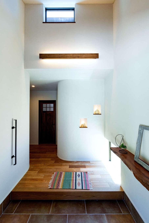 みずしまの家/水嶋建設【デザイン住宅、子育て、自然素材】吹抜けの玄関ホールは、上部の窓から淡い光が差し込み、温かみのある照明が引き立ち、美術館のように洗練された雰囲気が漂う。アールのカーブを描いた壁は大工の造作で、やわらかなトーンを醸し出している