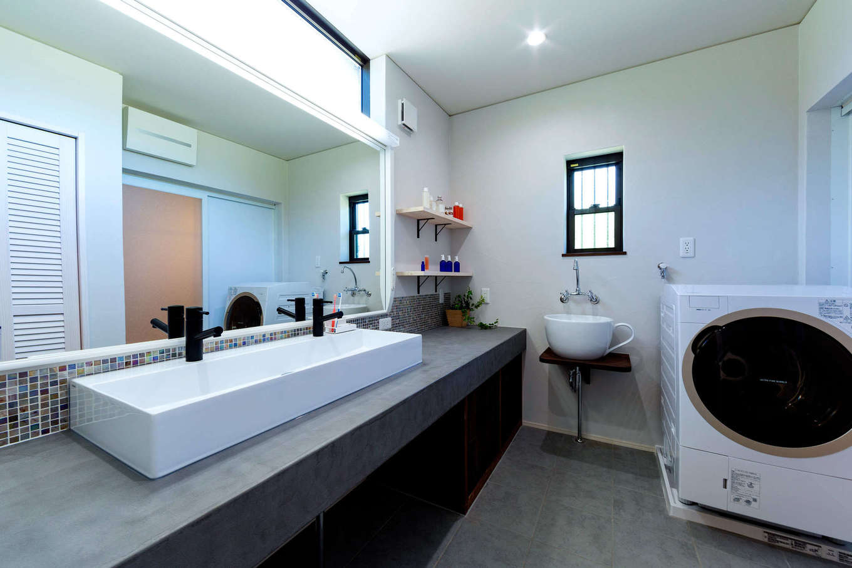 みずしまの家/水嶋建設【デザイン住宅、子育て、自然素材】洗面台は、柔軟性、強度、防水性、密着性に優れたモールテックスを採用し、ニュアンスを出した。床は冬場でもヒヤッとしないサーモタイル。コーヒーカップ型のボウルは、つけおき洗いができて便利。ワイドな鏡は、家族が横一列に並んで歯磨きできる