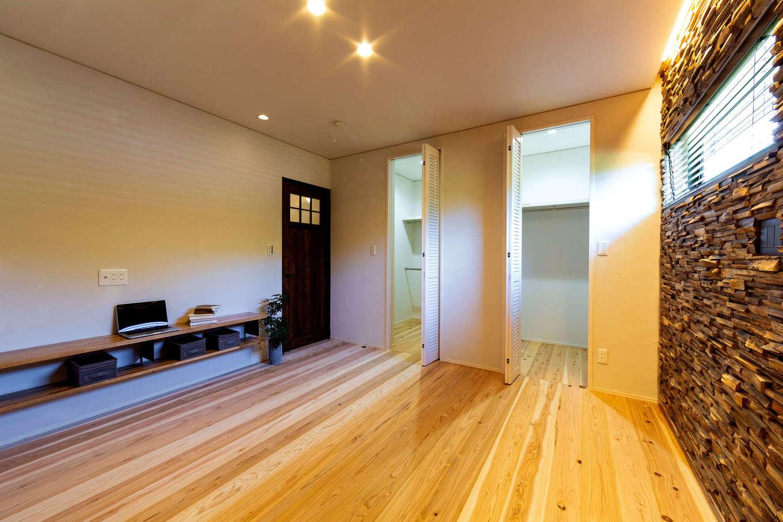 みずしまの家/水嶋建設【デザイン住宅、子育て、自然素材】年齢を重ねてからの暮らし考えると、1階に寝室を作るのは理にかなっている。床は無垢の杉材で、壁の一面には高級感あふれるウッドタイルを貼り付けた。大容量のウォークインクローゼットは、ご主人と奥さまそれぞれにスペースを区切り、使いやすくなっている