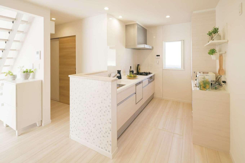 遠鉄ホーム【磐田市岩井・モデルハウス】対面式のオープンキッチンからは玄関やLDK全体を見渡せるので、帰宅した家族を「おかえり」と笑顔で迎えられる。キッチンの壁はモザイクタイルでオシャレ度アップ