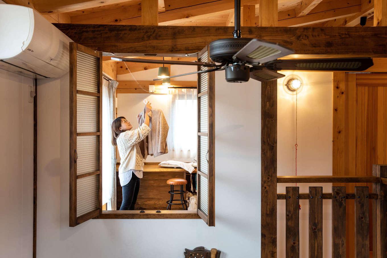 安形【デザイン住宅、自然素材、ペット】吹抜けの室内窓からインナーバルコニーを眺める。仕事を持つ奥さまは、室内干しが基本。寝室の隣にあるインナーバルコニーは南面に掃出窓とベランダがあり、日当たり良好。洗濯物もよく乾く。乾いたら家事カウンターでたたんだり、アイロンがけをしたりと、作業が一か所でできる
