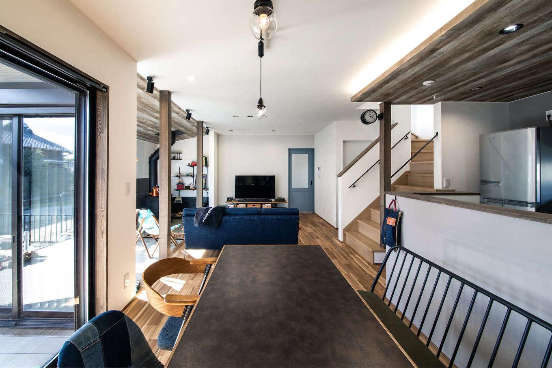 ナイスホーム【デザイン住宅、間取り、インテリア】大きな窓に視界が開けて、より開放感が増すダイニングキッチン。無垢の床の質感に合わせて家具や照明をコーディネートした。キッチンと土間リビングの天井に木目調のクロスを貼ってアクセントを
