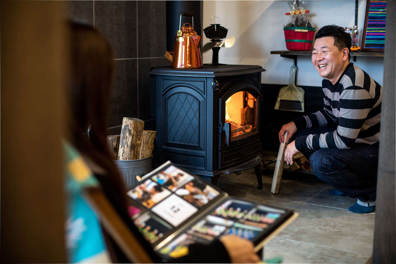 ナイスホーム【デザイン住宅、間取り、インテリア】ご主人のたっての希望で、土間リビングに薪ストーブをしつらえた。薪をくべる手間さえ嬉しくて、この笑顔