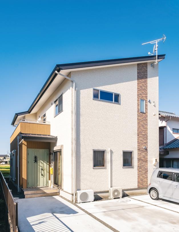 片流れの屋根ですっきりと整えられた外観。レンガ調のラインや淡いグリーンの玄関ドアでナチュラルな印象