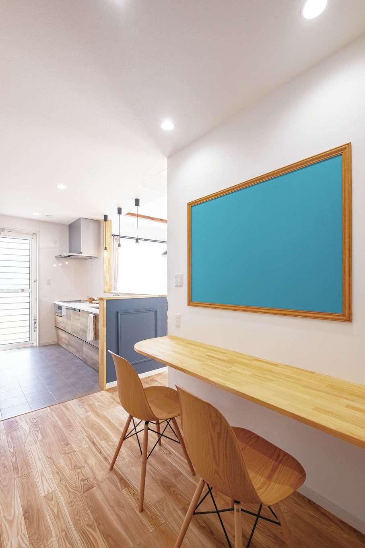 Art Wood Home (永建)【子育て、間取り、デザイン住宅】キッチンのすぐ隣にはスタディーカウンター、壁にはブルーの大きなマジックボードを設置。ママはキッチンに立ちながら子ども達の様子をうかがえる。子ども達が成長した後はママが利用する予定。子どもカウンター奥には、ママ用おこもりスペースのデスクもあり、いつも家族の気配を感じながら過ごせるリビング周りに