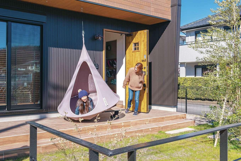 家の顔ともいえる玄関ポーチ。リビングから続くテラスはゆったりと広く、庭とはまた違ったオープンエアの空間。家の中にいる奥さまも、外で遊ぶ子どもも、お互いに様子がわかるので、安心できる遊び場だ