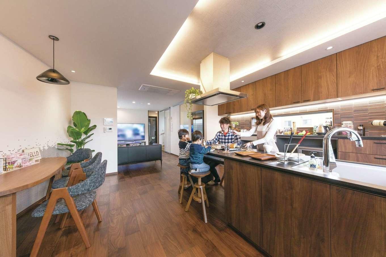 建築システム(狭小住宅専門店)【浜松市中区助信町9-16・モデルハウス】シックなヴィンテージ調にまとめられたLDK。門型フレームを採用し、2階部分はワンフロアの大空間を実現。キッチンダイニングは縦の広がりを生み出す上げ天井にし間接照明で空間を演出する。壁一面の大容量収納に加えて、アイランドキッチンにもたっぷりの収納スペースを完備。すっきりと片付けられる設備選びの参考にしたい