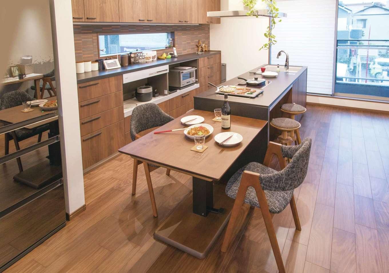 建築システム(狭小住宅専門店)【浜松市中区助信町9-16・モデルハウス】来客と一緒に食事を楽しむ時は、キッチンにテーブルを付けて。リビングのセンターテーブルは天板が昇降するタイプなので、ダイニングでの兼用が可能。こうしたアイデアの提供で、狭小住宅での暮らしやすさの提案もしている