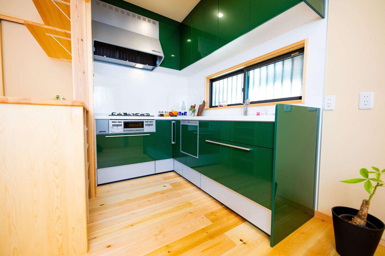 だいはるの家/大春建設【子育て、自然素材、狭小住宅】限られたスペースを有効に使うため、キッチンはL字型に。奥さまからのリクエストに応えて、鮮やかなグリーンのキッチンパネルを採用した