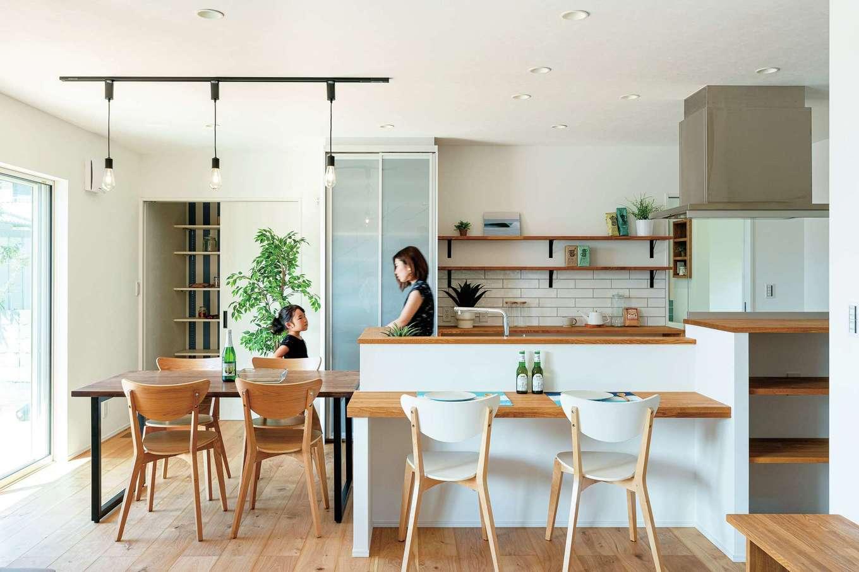 KureKen 榑林建設【デザイン住宅、省エネ、間取り】「既製品は好きじゃなくて」という夫妻は、カウンターや棚を造作仕立てに。左奥はパントリーで、右奥は水回り。横並びのダイニングテーブルとともに、家事効率アップに貢献