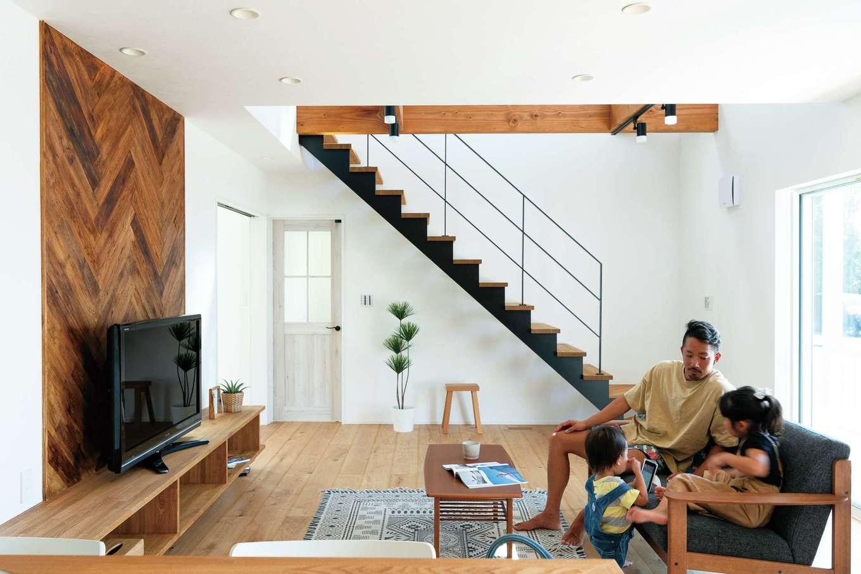 KureKen 榑林建設【デザイン住宅、省エネ、間取り】吹き抜けの開放感と無垢オークが放つぬくもりをアイアンの階段が引き締める。造作テレビ台の背後に斜めに張られたタモは、1枚ごとアンティーク加工を施したもの。視線を落ち着かせつつ、空間のアクセントになっている
