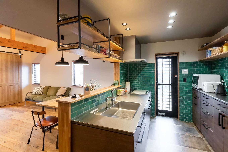 尾崎工務店【デザイン住宅、収納力、ガレージ】カフェスタイルのオープンキッチンは奥さまのこだわり。木とアイアンとグリーンのサブウェイタイルが絶妙に調和し、料理タイムを楽しく演出。子どもがどこにいても見渡せて安心できるのもいい