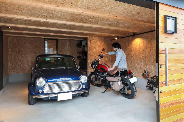 尾崎工務店【デザイン住宅、収納力、ガレージ】ご主人の夢を叶えたビルトインガレージ。車とバイクと折りたたみ式自転車を入れてもまだ余裕がある。水栓設備と収納も充実。外観デザインとのバランスを考慮して、シャッターではなく木製の一枚引き戸を採用した