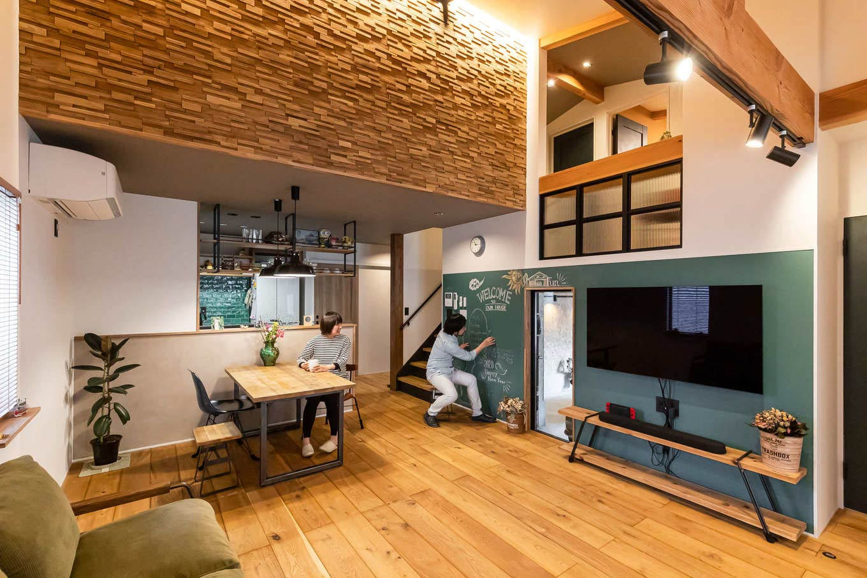 尾崎工務店【デザイン住宅、収納力、ガレージ】勾配天井を活かしたハーフ吹抜けのリビング。ウッドタイルが空間のアクセントに。幅広の床は無垢のオークで床暖房仕様。家具や照明も床の質感、色に合わせてコーディネートされている
