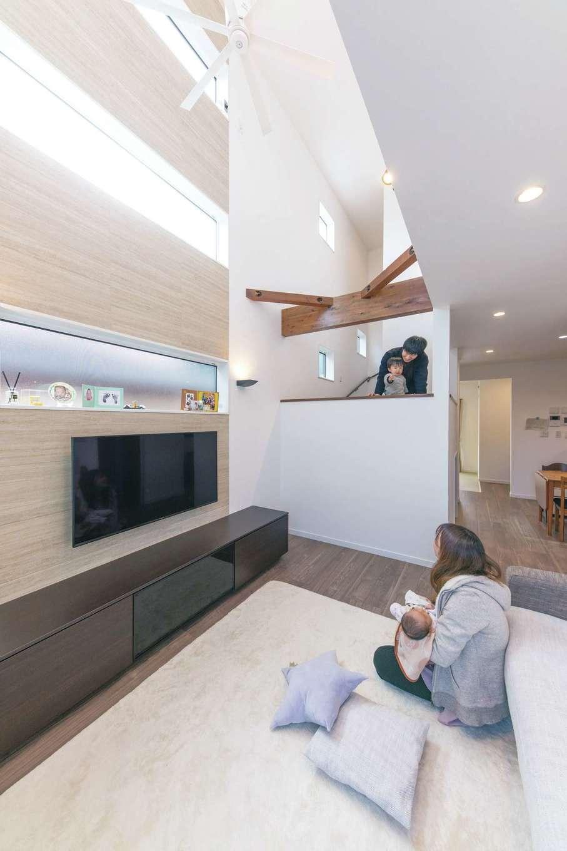 三和建設【収納力、屋上バルコニー、スキップフロア】南側に家が隣接しているため、吹き抜けで高所から光を取り込んだ。TV背面の壁には調湿・消臭効果のあるエコカラットを天井まで