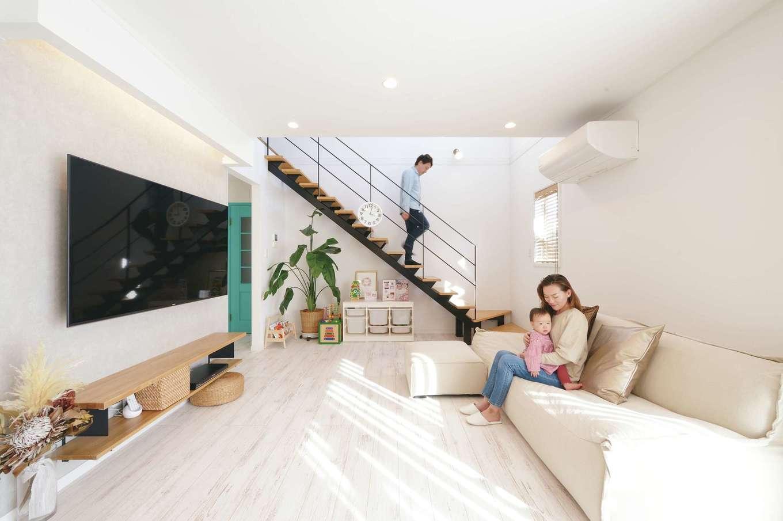 ハートホーム【子育て、輸入住宅、間取り】吹抜けと南面の窓からたっぷりの光が降り注ぐリビング。白を基調とした室内に黒いスチール階段、グリーンの建具が映える。シャビーなテイストのフローリングは床暖房仕様でほんのり暖かい