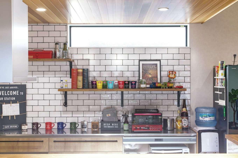 甲静ハウジング【子育て、間取り、ガレージ】キッチン背面の壁はSNSなどを参考に「こんな感じ」と伝えて棚をつけた。カラフルな小物が白タイルに映える