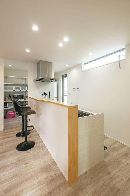 ティアラホームスタイル【デザイン住宅、間取り、ペット】キッチン腰壁の天板を一部広げてカウンターとして使えるようにした。奥のパントリーは行き来しやすいウォークスルータイプ