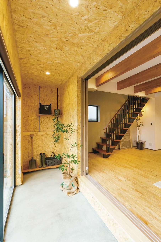 タツミハウジング【デザイン住宅、狭小住宅、間取り】玄関を入ると、リビングの広い土間に繋がっている。壁はOSB合板張り。土間の奥にはご主人のサーフィンラックがあり、仲間に羨ましがられているそう