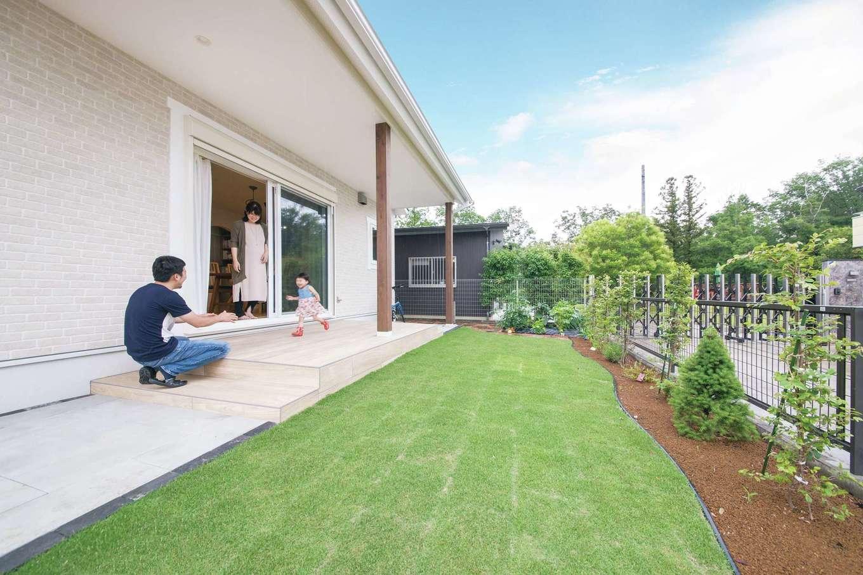 小幡建設【デザイン住宅、子育て、省エネ】青々とした芝生の庭と、LDKをつなぐ軒下のデッキは、室内との一体感とメンテナンスのしやすさを考慮し、木目調のタイルをセレクトした