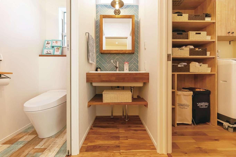 丸昇彦坂建設【デザイン住宅、子育て、間取り】誰かが入浴中でも利用できるよう、洗面室と脱衣室を分けた。造作の洗面台は、泥んこのズックも洗える深底シンク、ヘリンボーン張りのタイル、木枠の鏡を採用し、朝からテンションが上がる