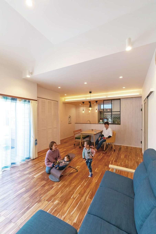 丸昇彦坂建設【デザイン住宅、子育て、間取り】開放感あふれるリビングダイニング。アカシアの床の上を子どもたちが走り回る。ダイニングとリビングで天井高を変えたことで、より空間が広く感じられる。大きな窓を開ければウッドデッキ、庭へとつながる