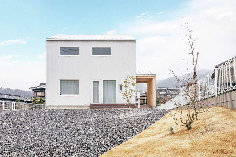 共感住宅 ray-out (レイアウト)【デザイン住宅、子育て、省エネ】三角屋根のころんとしたフォルムが素敵な白ガルバリウムの外観。小屋のような板張りのポーチがアクセントに。広い土地でも、芝生の面積を広げすぎないことで、無理なく手入れできる庭を目指した。通り側に位置しているけれど、奥まっているので視線が気にならない