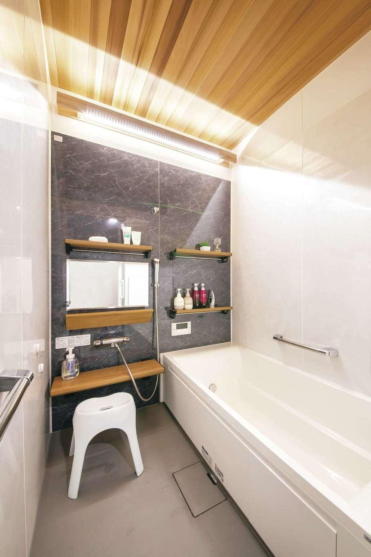 T-style 【デザイン住宅、子育て、省エネ】「木目の天井と間接照明のおかげで、温泉気分を味わえます」とご主人。バスルームの天井が高いため、ゆったりと広く感じられる