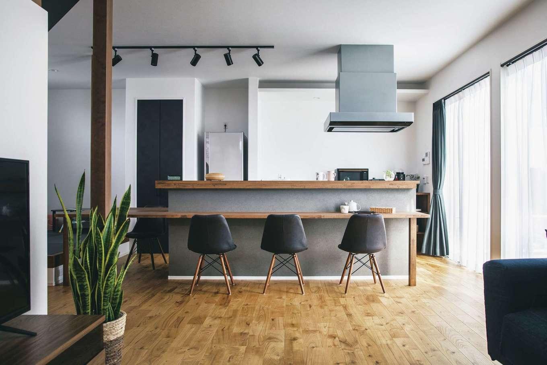 ワンズホーム【デザイン住宅、間取り、建築家】家の主役は、造作カウンターとダイニングテーブルが一続きになるキッチン。カウンター上部に間接照明が設置され、夜はバーのような雰囲気になる。共働きで家事は分担制、ご主人が料理することも多く、キッチンは2人がすれ違えるほど広々。シックな木の色合い、グレーの壁紙、黒いアイテムのバランスにセンスが光る。高い気密性と断熱性、24時間空気が循環する換気システムのおかげで、「2階洗面所のエアコン一台で1階まで快適です」そうKさんは笑う