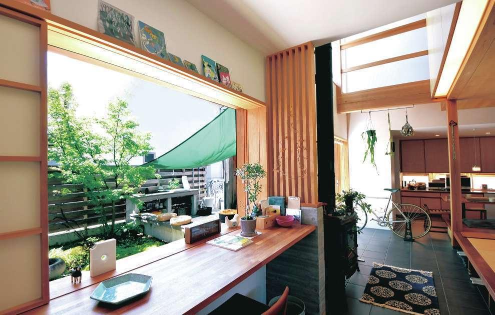 桂建設【浜松市東区天王町1930・モデルハウス】外と中を繋ぐ中間領域として、土間を設置。玄関を開けると、タイル張りの土間がキッチンまで続く。庭に面したカウンターに座って眺める景色に心が癒される。窓の木製サッシや格子の網戸はオリジナルの造作。壁の中にサッシをインセットできるので、視界がいっそう広がる