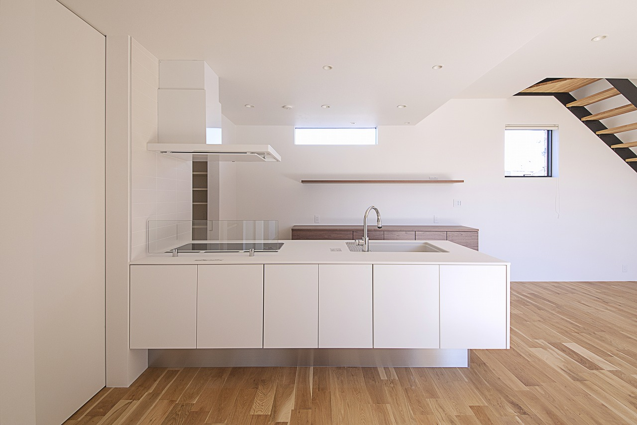 背面にはオープンラックを設け、シンプルな空間に器やグリーンを飾って彩りをプラス。キッチンの脇にはパントリーがある