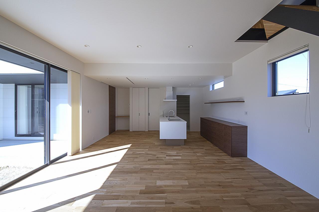 キッチンをリビングの入り口に向けて配置したことで、帰宅した家族を真正面から迎えられる。壁面の棚には見せたいものを飾り、それ以外はパントリーに隠して収納