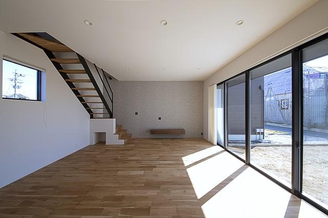 ナラの床とアイアンの階段、本物の素材ならではの質感が上質な心地よさを創出。階段の下には掃除ロボットの基地を設けた