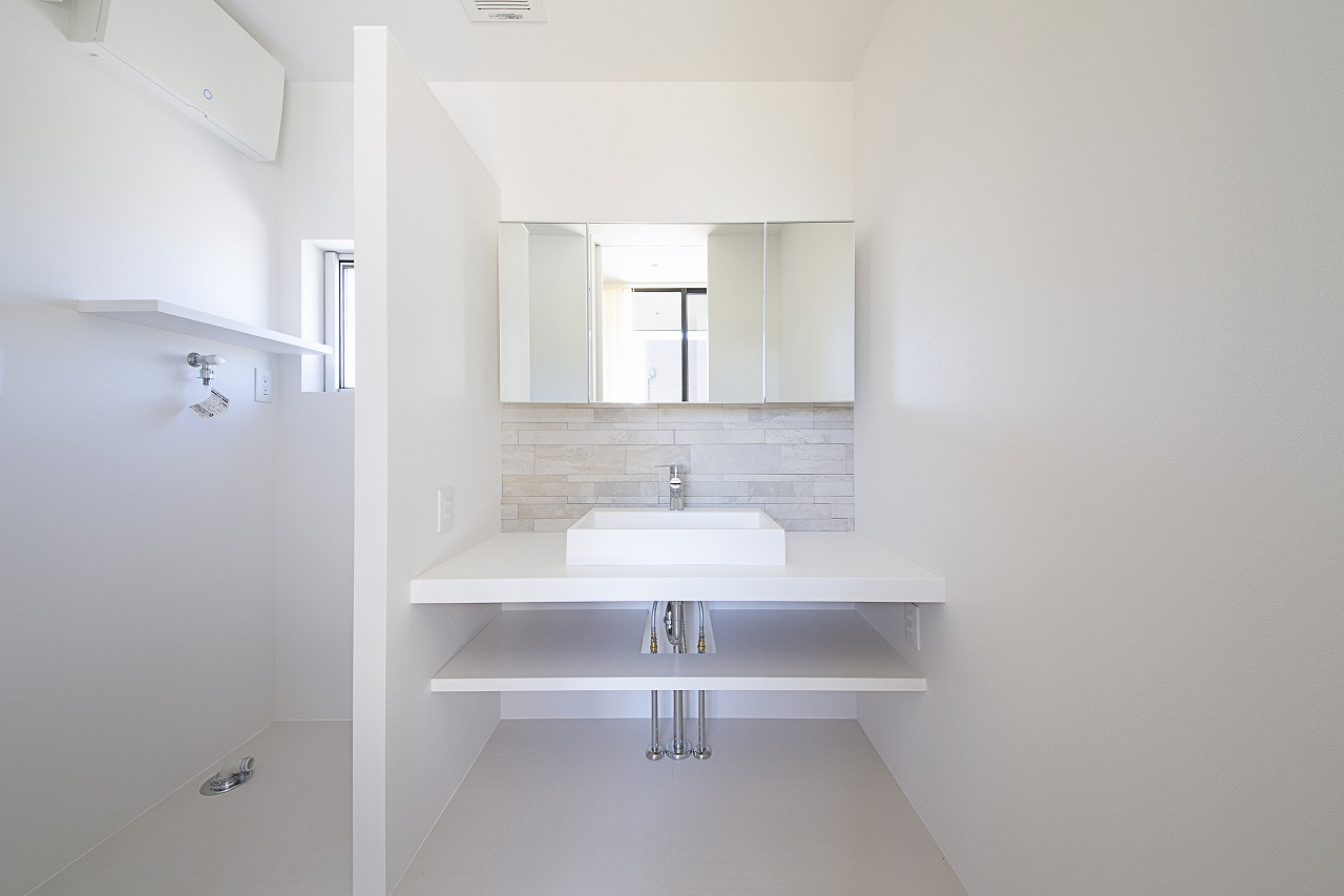 洗面と脱衣スペースは白で統一し、壁で仕切って配置