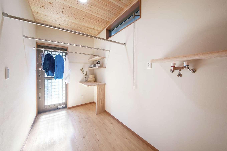 住まいるコーポレーション【デザイン住宅、自然素材、間取り】キッチンのすぐ後ろにランドリーを設け、家事をする場所を集約。ランドリーには室内干し用のポールや家事カウンターがあり、勝手口の先のテラスに外干しもできる