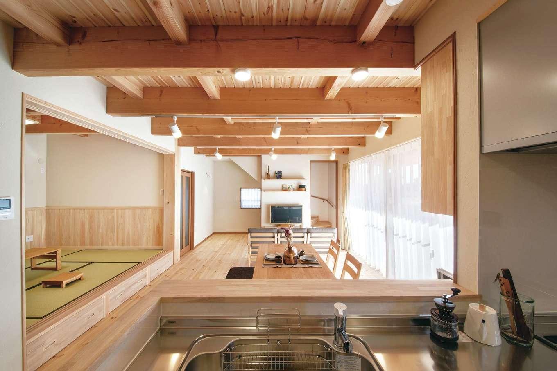 住まいるコーポレーション【デザイン住宅、自然素材、間取り】対面キッチンに立つと、室内がすべて見渡せる。また、奥さまが冷え性のため、エアコンの暖気が2階へ逃げないように階段を引き戸で仕切れるようにした